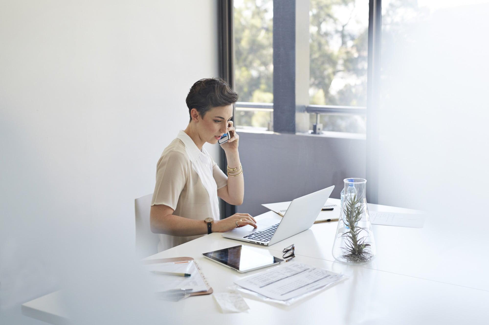 Mulher em frente ao computador buscando sobre controle de notas fiscais