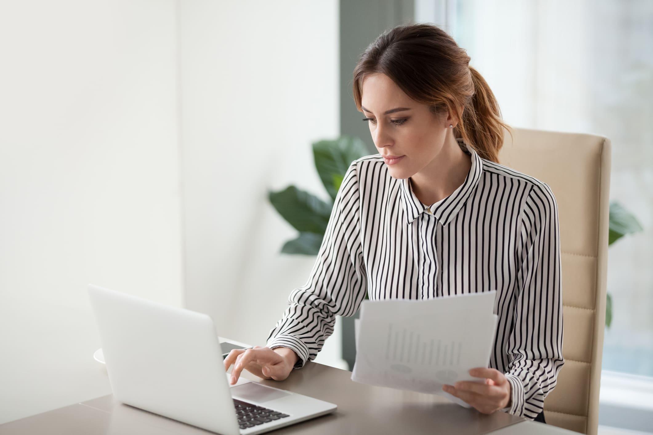 Mulher em frente ao computador calculando SPED ICMS.