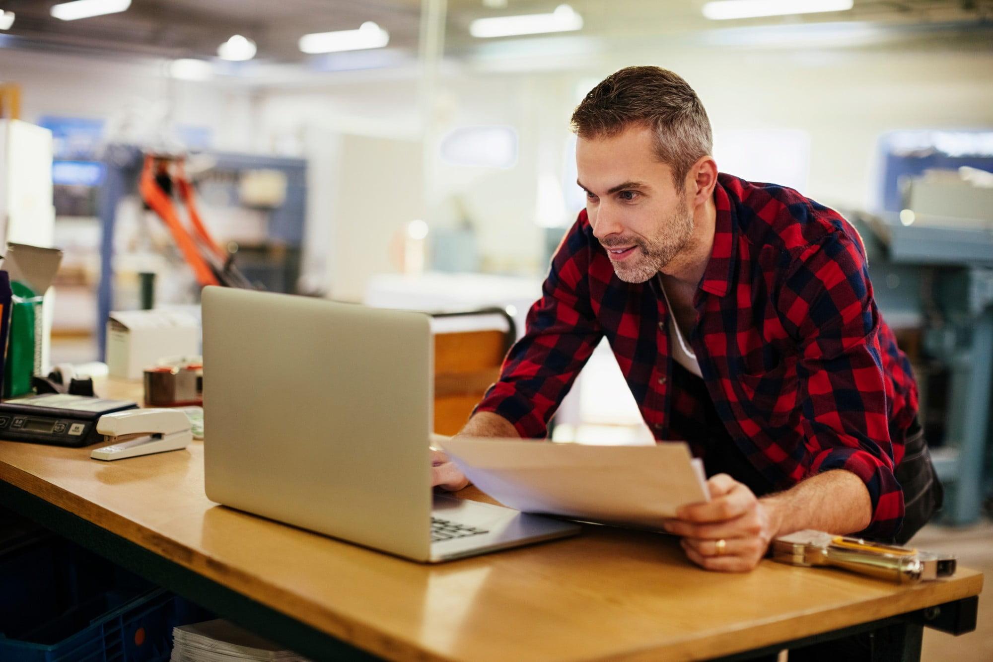 Homem em frente ao computador analisando notas em contingência off-line
